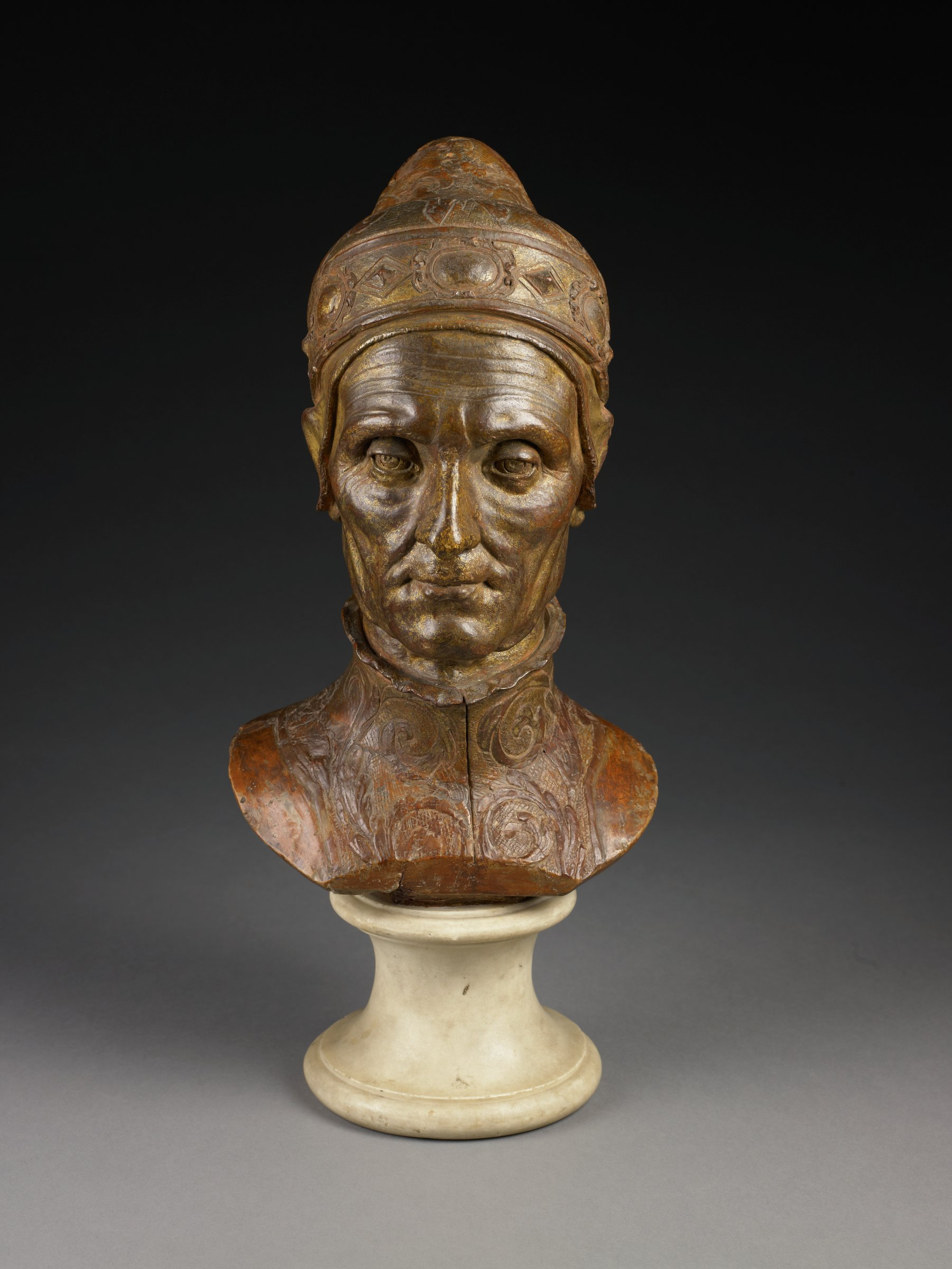 "This terracotta is a nearly life sized bust of the aging sitter. He wears the doge's official ""corno ducale,"" with its jeweled rim and brocaded bonnet. Beneath the hat is a thin cap, carefully modeled over the ears. His garment is also brocaded, with a crimped collar. The Doge's face is lined with incised wrinkles, and modeled to give the appearance of sagging skin. The cornea and retina are also incised."