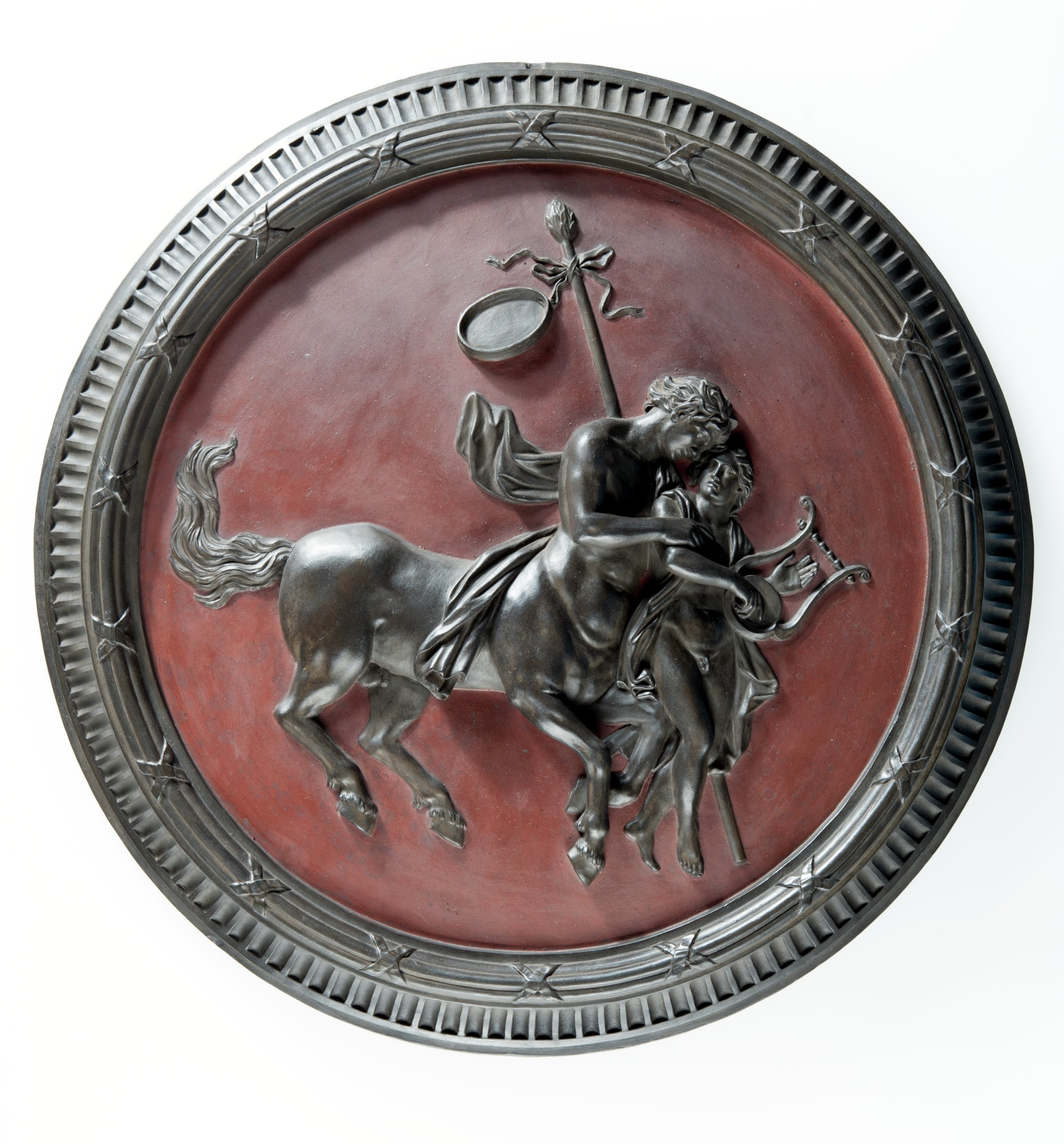 Large round, self-framed plaque of black basalt with the image of a Centaur teaching Achilles the Lyre against a red encaustic ground.