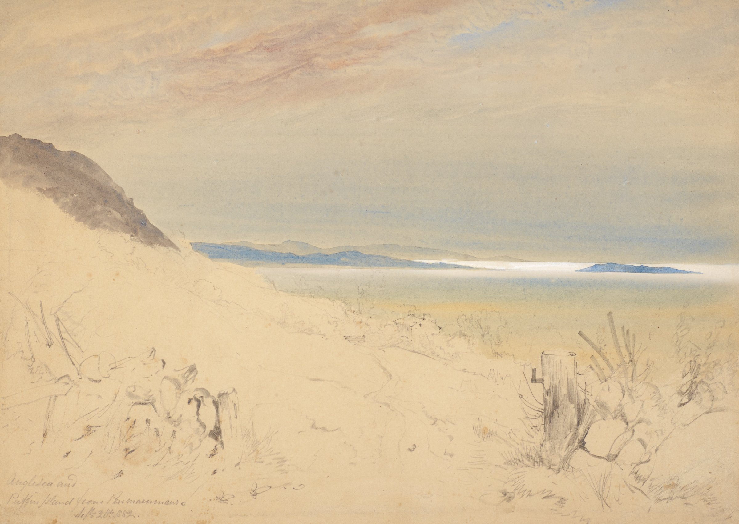 View of a mountainous coast from a sandy beach. Two short wooden posts mark a pathway in the foreground.