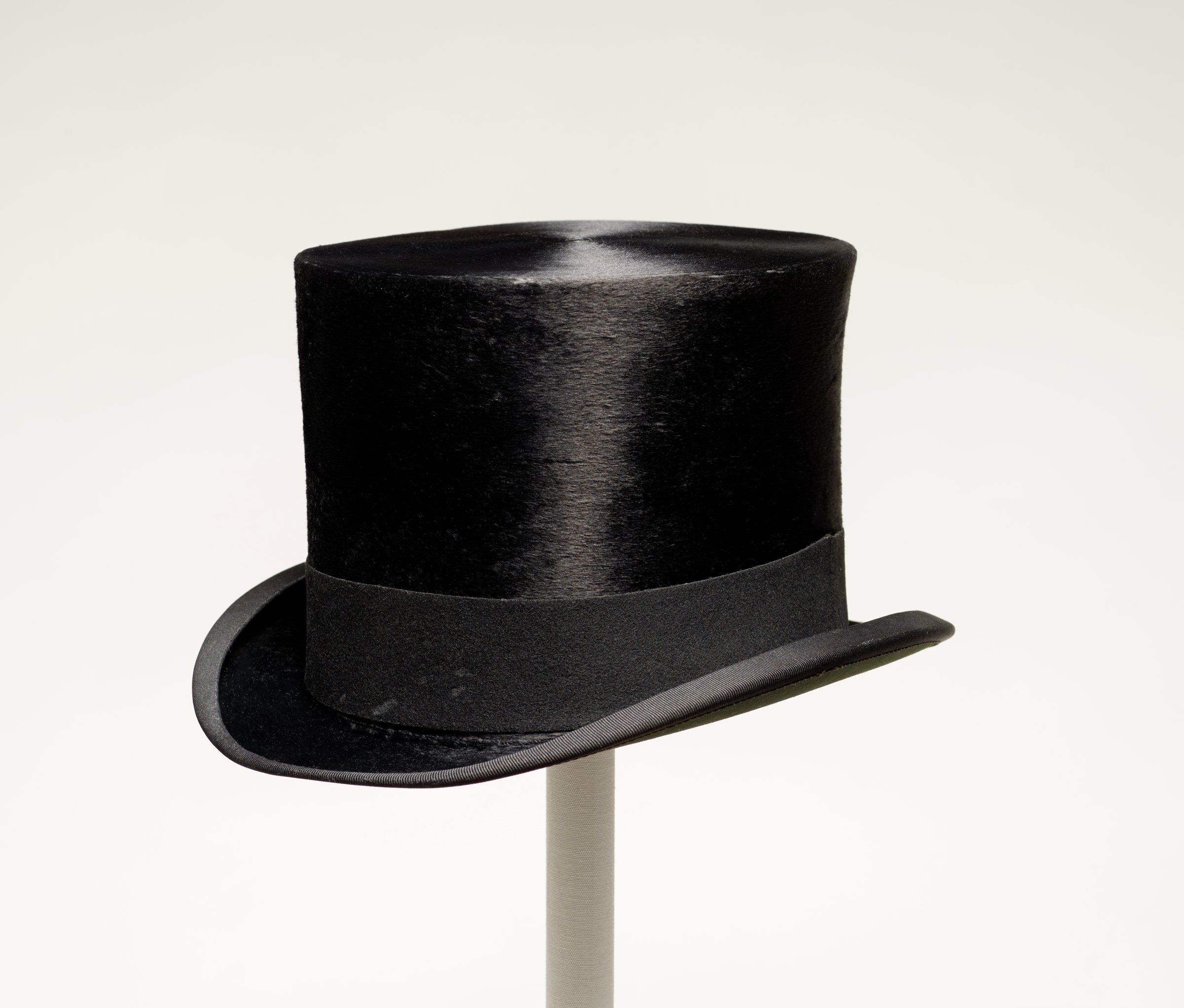 Man's top hat of beaver felt with a grosgrain ribbon band and brown leather sweatband around the inside, lined in a light yellow silk.