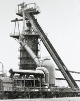 A closely cropped, evenly lit black and white photograph of an industrial Alabama blast furnace