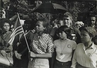 A crowd of people standing run from left to right across the image. (They are outside of 16th Street Baptist Church, attending the funeral of Addie Mae Collins, Cynthia Wesley, and Denise McNair. From left to right they are: Emma Bell, Dorie Ladner, Dona Richards, Sam Shirah, and Doris Derby.) One member of the crowd holds an American flag.