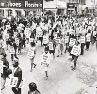 "This black-and-white photograph captures demonstrators marching down Main Street in Memphis holding placards that read, ""Honor King: End Racism"" and ""Union Justice Now."" The sign for Florsheim Shoes appears at top left."