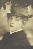 In this black and white photograph, a woman fills the image. She turns her head to face the camera, looking out of the left corners of her eyes with her lips slightly parted. She wears a hat and a black garment, from under which a sliver of a white collar is seen. Above her head are out of focus shapes that look like leaves.
