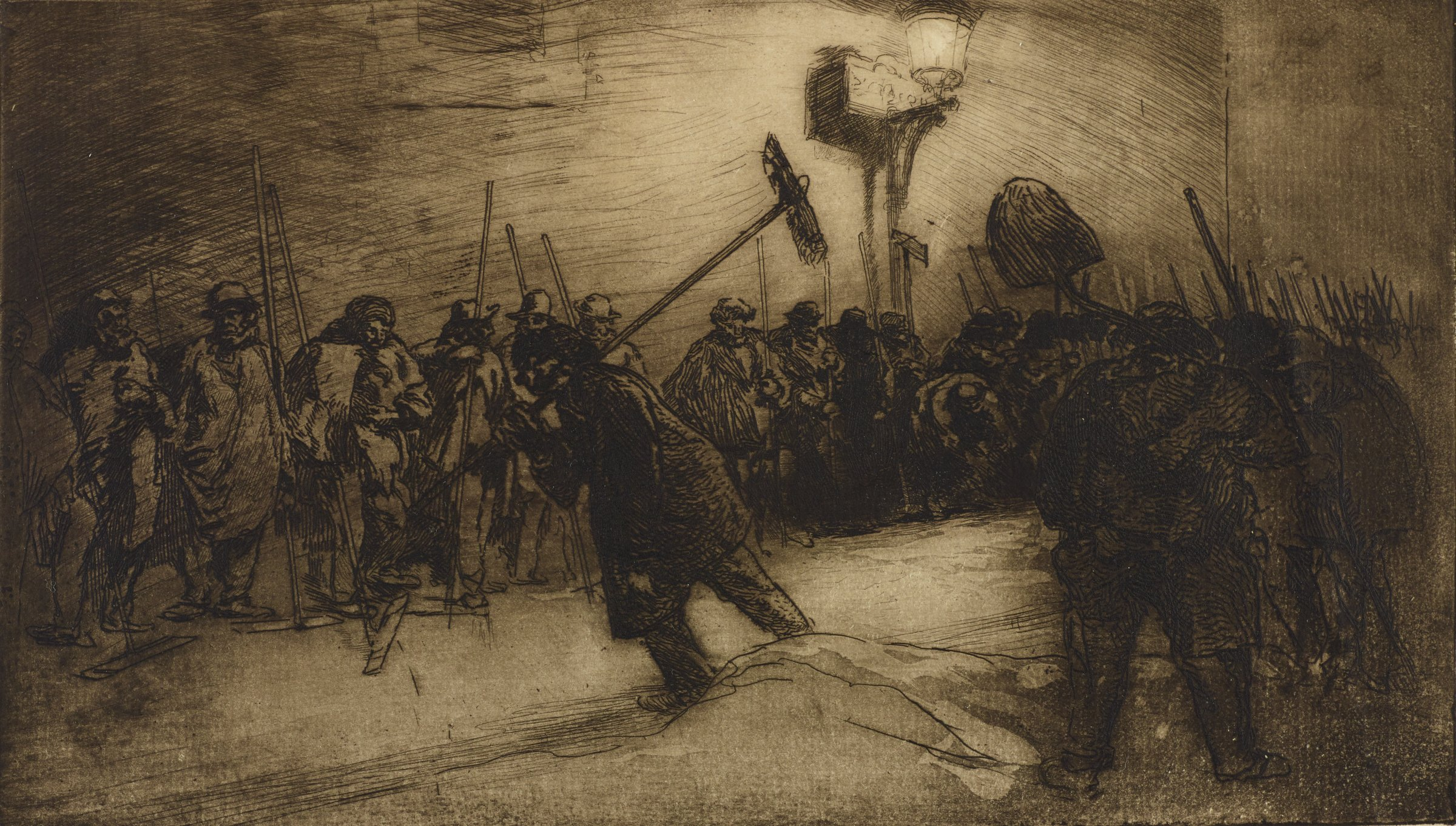 Men with shovels and brooms line the street. A single man walks through the middle of the crowd holding a broom over his shoulder.