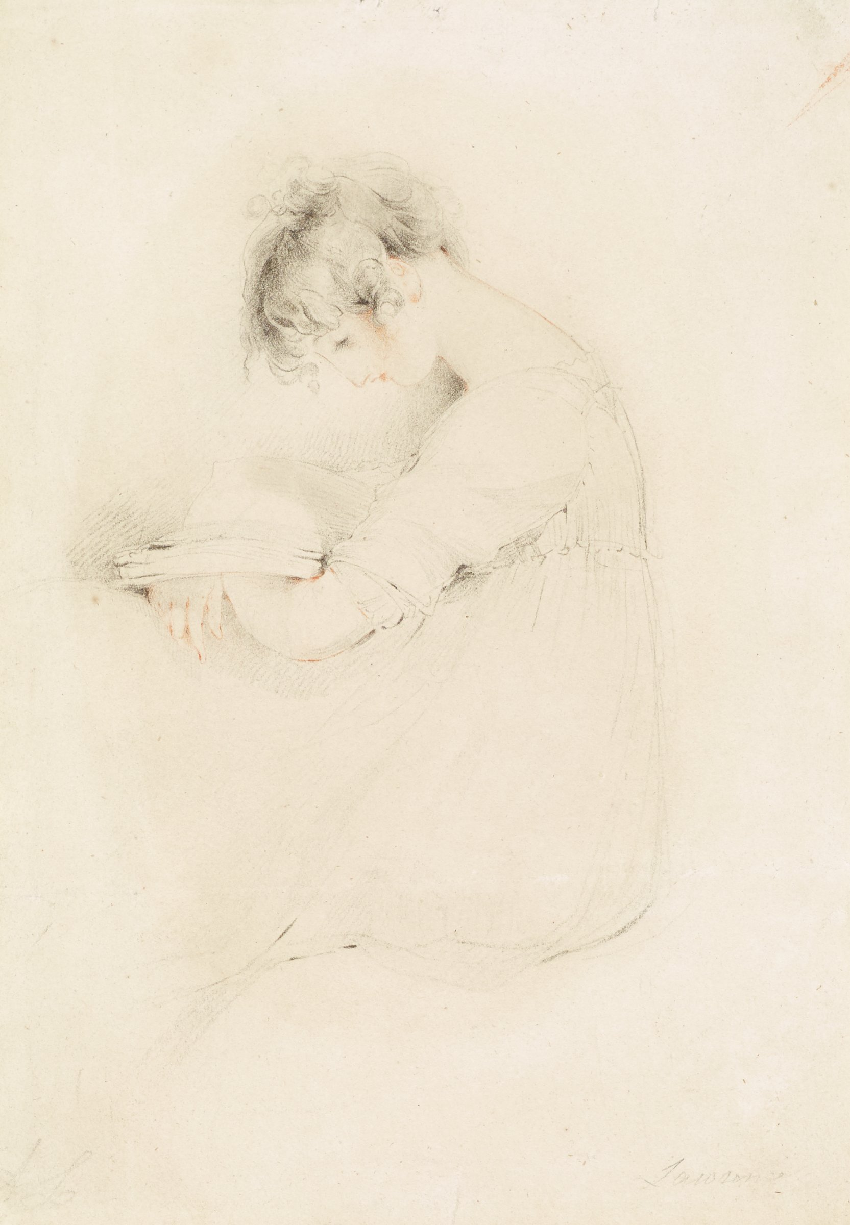 A woman cradles an open book in her arms as she leans on a table and lowers her gaze to read.