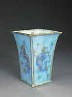 """Bone china """"dragon lustre"""" vase of square shape with flared lip, the exterior glaze a runny, mottled luster blue with gilt borders in a lattice pattern at bottom, along each side edge, and at the outer lip, each side is decorated in gold with a stylized dragon, the interior a lighter turquoise color with, on two sides, a dragon motif, and on two sides a symbolic motif, inside the lip a border of gilt flower and leaf design."""