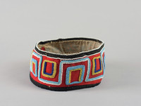 Red felt ground backed with black cloth. Floral designs in white, blue, yellow and a rusted metallic bead. Edge with black cloth and white beads. Two brass snaps.