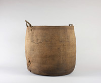 Large spruce root basket; folded; weave is tighter at the top; two thong handles. Inside are some fragments of cedar bark basket.