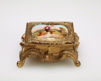 Small gilft bronze stamp box in the Rococo style with scrolled legs and on the lid a shell motif surrounding a porcelain insert decorated in enamel colors with a male figure in a landscape with baskets of flowers.
