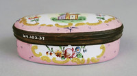 Pink oval box with painting of a castle on top.