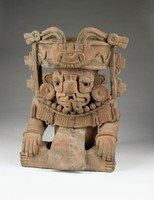 Cylindrical urn depicting personage sitting cross-legged with hands resting on feet. Figure wears elaborate headdress and mask; forked tongue emerges from open mouth.