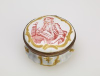"""Small, round enameled copper box with white ground and gold highlights, on the lid in a reserve enclosed by gold scrolls, the printed portrait of a seated woman in red, the interior inscribed with """"VOUS APPAS AIMES MES BIAS."""""""