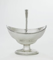 Simple, canoe-shaped silver basket raised on oval foot with reeded edge, the body likewise with a band of reeding at the upper edge, otherwise, plain, with reeded swing handle.