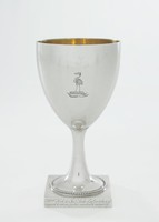 """Tulip-shaped silver goblet with beaded round foot resting on a square base, the base engraved on one side with the date MDCCLXXXIII and on the other """"Wm Hole to Jas Luke Esqr in token of regard & esteem for his candour & integrity,"""" the main body engraved on one side with a crane on a """"chapeau gules turned up ermine"""" – traditionally the emblem of the Crane family – the interior covered with a gold wash."""