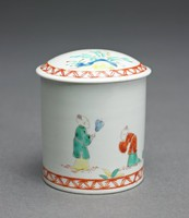 Small covered rouge pot of white porcelain decorated in iron red, green, blue and yellow with Asian figures and foliage and with at the foot and around the rim of the domed cover a band with chevron motifs in iron red.