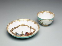 Tea bowl and saucer of white porcelain with web-type gilded borders and exterior Robin's egg blue ground, the tea bowl with large reserves containing finely painted harbor scenes, the interior white, the saucer with same Robin's egg blue ground and large reserve in the center with harbor scene.