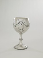 """One of a pair (with 1972.277) of silver wine goblets, each with a bulbous cup resting on a slender stem that is divided into two parts by a slightly flared, beaded """"waist,"""" the round foot stepped and with a beaded edge, the main body decorated with leafy floral garlands and ribbons that support on either side an empty roundel that would have held the owners crest or initials (the decoration perhaps later), the interior is covered with a gold wash."""
