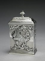 Small silver tea canister of narrow, rectangular form with molded borders and hinged stepped domed cover with flattened rectangular urn finial and lock on one side, the body heavily decorated in the Rococo style with shellwork, scrolling foliage, flowers and engraved fish scale motifs, on one side in a reserve comprised of leafy floral elements the engraved initials FW (?), on the other in a similar reserve a coat-of-arms, the cover and finial engraved with stylized leafy flowers.