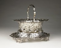Intricate stand of finely chased silver designed to support a matching basket, resting on four heavy, scrolled feet with shell motifs, the pierced stand curves inward and upward in a dynamic pattern of scrolling foliage and flowers, the lower edge irregular and centered on each of the four sides with a cast and applied mask, the upper edge likewise irregular and ornamented with foliage, with four undecorated edges at which rest the feet of the basket.