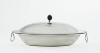Simple, silver oval dish and domed cover with beaded edge, with two hinged handles of modified heart shape, the cover with wooden ball knop, engraved on the interior lip of the body and on one side of the cover, a demi-lion rampant holding a shield with pile and hatchings (unidentified).