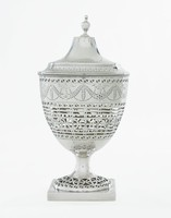 Squat, urn-shaped silver covered sugar bowl resting on a square base that is decorated with bright-cut engraving in a pattern of floral motifs at the corners and bands of squiggly dots between, the round, pierced foot decorated with stylized floral elements in roundels, the body with a pierced middle section in a repetitive geometric pattern that mirrors the decoration on the foot, the upper body engraved with empty circular reserves and leafy and dot swag motifs, the neck with a pierced wavescroll band below a beaded edge, the elongated, domed cover likewise engraved on the inverted shoulder with bands of repeating dots, scallops, and ovals, with small urn finial.