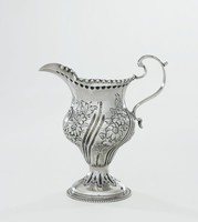 Small silver, modified helmet-shaped creamer on splayed, round, gadrooned and beaded foot, the main body decorated with a punched floral design between deep, slightly curved lines, with scrolled handle and long beak-like spout, the rim decorated with bold punch marks, in a reserve under the spout the initials WMA.