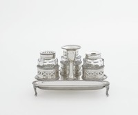 Small silver inkwell resting on three fluted, slightly curved legs, with beaded edges, comprised of four parts – a pen tray and stand with attached candleholder (with hook for a snuffer, now missing) and three cut-glass vessels with silver covers for ink and sand, these rest in detachable, pierced silver galleries held in place from below with pins.