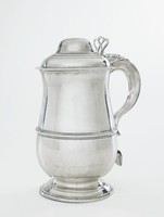 Simple, plain, large silver tankard of waisted, baluster-shape, on round, stepped foot, with double C-scroll handle that terminates in a heart-shaped motif, with hinged, domed lid, at the hinge a decorative, applied, strap element, with open scroll thumb piece.