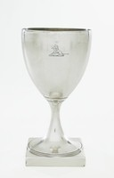 One of a pair of simple silver goblets (with 1972.317), each with a flared stem on round, beaded foot that rests on a square base, on one side of each is engraved a crest of a seated lion (unidentified), the interiors with a light gold wash.