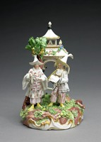 Figural group in the form of a Chinese-style pavillion, or pagoda, behind two figures in Chinese garb, one playing the flute, the other a triangle, on naturalistic base covered with grass, flowers and rocks, highlighted in gold.