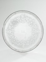 Large silver salver resting on four flat, tapered, threaded legs with stubby feet, the edge beaded, the interior rim decorated with bright cut engraving in a repeating pattern of strapwork and ovals with crosshatching, the well heavily decorated with a bold, wide band of bright cut engraving in a pattern of scrolls, shells, and strapwork, the center left empty except for an engraved crest in the form of a winged demi leopard or lion guardant (unidentified).