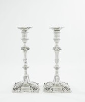 Pair of ornate candlesticks, each on shaped square base cast with Rococo shell and foliate motifs, the knopped baluster stem with similar foliate decoration, the spool-shaped socket with plain central band and two rope-like bands one each above and below, the detachable nozzles likewise with foliate ornamentation, both the base and the nozzle engraved with a lion passant over crown crest (unidentified).