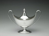 One of a pair (with 1973.3a-b) of silver, boat-shaped, covered sauceboats, each raised on stepped oval foot with beaded edge, the upper rim of the main body likewise beaded, with two large, loop handles with reeded accents, the fitted, domed cover notched to accommodate a ladle, with beaded urn finial, both the cover and the body on one side engraved with a stag crest.