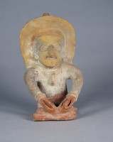 Seated figure with ornate headdress, nose ring, earring