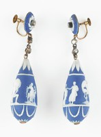 """Pair of teardrop-shaped earrings of dark blue jasper with white jasper bas relief, each earring suspended on a short chain set with two jargoons (faux stones) and hanging from a round dark-blue jasper medallion with white jasper bas relief in a pinwheel pattern and with a jargoon in the center, with gold screw back, the drops each with stiff leaf pattern above and beaded swags below, in the middle of each a series of classical figures comprised of .1) """"Hercules strangling the Nemean Lion""""; """"Terpsichore""""; """"Hercules supporting the world""""; and """"Diana with stag""""; and .2) """"Hercules strangling the Nemean Lion""""; """"classical male figure""""; """"Hercules supporting the world""""; and """"classical male and female figures."""""""