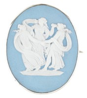 Small oval medallion of solid light blue jasper with white jasper bas relief of The Three Graces – the dispensers of Liberality, Eloquence and Wisdom as three classically dressed young women dancing in a circle with hands clasped – in simple silver mount with horizontal pin behind.