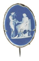 Small oval medallion of white and dark blue jasper laminated and lapidary polished with white bas relief of a seated classical woman with attendant, in simple brass mount with vertical pin closure on the back.