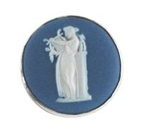 Hat pin comprised of a round medallion of white jasper with dark blue dip with white jasper bas relief of Terpsichore—a classical female figure holding a lyre standing next to a column with a figure on top—in a simple silver mount with long silver pin.