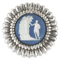 Small round button comprised of a dark blue jasper medallion with white jasper bas relief of Perseus and Andromeda – Andromeda steps down from the rock, her left hand is supported by Perseus – in a cut-steel mount with gadrooned border, with eye on back.
