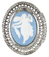 Oval buckle comprised of a solid light blue jasper medallion with white jasper bas relief of Psyche – a classically draped, floating female figure with butterfly wings holding a draped cloth – set into a pierced and beaded cut steel mount.