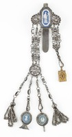"""Chatelaine of cut steel, the large steel hook set with an octagonal medallion of solid dark blue jasper with white jasper bas relief of a standing classical figure next to a column holding a mirror in her left hand and surrounded by a stiff leaf border, on either side large, round beaded florettes of cut steel from which extend three chains united on one side by a similar round beaded element and on the other by a hook, from the beaded element extend four additional chains, two of which end in beaded tassels, one has attached a round solid blue jasper medallion with white jasper bas relief of on one side """"Hebe and the Eagle"""" and on the other a striding classical figure set into a seal, and the last has attached a round solid blue jasper medallion with white jasper bas relief of on one side Hebe and the Eagle and on the other a group of classical figures at an altar set into a key; attached to the hook on the other side is a small, delicate tooled gold book with ivory leaves."""