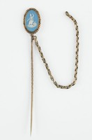 Small stick pin comprised of an oval, double-sided, light blue jasper medallion with white jasper bas relief of on one side Jupiter – Jupiter seated with staff and eagle – and on the other Venus and Cupid set in a gold ropework mount on gold pin with a simple gold chain attached.