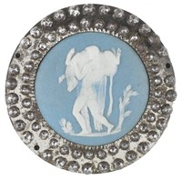 Small round button comprised of a solid light blue jasper medallion with white jasper bas relief of Hercules and the Cretan Bull – Hercules carrying the slain Cretan Bull over his shoulder – set in a cut steel mount set with two rows of faceted beads of cut steel, the reverse of the mount pierced in a spoke pattern.