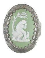 """Oval medallion of white jasper with green dip and white bas relief of the """"Bourbonnais Shepherd"""" – a young man seated under a tree with a small sheep in his arms and a small dog looking on – mounted in a steel bracelet, the medallion held to the face with prongs, the surrounding border engraved with crosshatching and on either side a simple flower with leafy motifs, the band is attached to the face with hinges and is engraved with a stippled border and on either side a triangle with similar leafy motifs, with adjustable hook and chain clasp."""