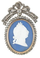 Pendant comprised of an oval, solid dark blue jasper medallion with white jasper bas relief of King George III in profile right with laurel leaf crown, set into a textured gold frame and mounted in silver adorned with a band of jargoons, or faux stones, which hangs from a decorative element in the shape of a large bow set with smaller jargoons and with a larger stone in the center of the bow, with an eye behind for a chain.