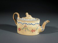 """Small oval teapot of light buff-colored caneware, the upper body molded to look as though it has an irregular, """"feather-edged"""" border picked out in bright blue enamel, the lower body decorated with a series of floral garlands that run around the body — bright red roses, small blue flowers, green leaves — the upper edge with a band of white enamel highlighted with stylized green anthemion motifs between dot borders, the ear-shaped handle molded with modest leafy décor, the gently curved spout with similar """"feather edge"""" molding highlighted in blue, the flat cover with the same white enamel border and molded decoration picked out in blue, with recumbent spaniel as knop."""