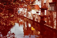 Canal edged with houses on one side, foliage on the other