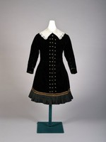 Black velvet with gold buttons down front, bottom banded with three rows of gold braid and edged with pleated black taffeta