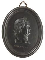 Oval medallion of black basalt with bas relief portrait bust of Roman Emperor Vespatian (9-79 AD) facing right, wearing laurel leaf crown, the name VESPATIAN impressed below the truncation, self frame, pierced to hang.